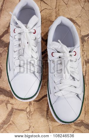 Pair Of White Fashionable Laced Trainers On Wooden Surface.