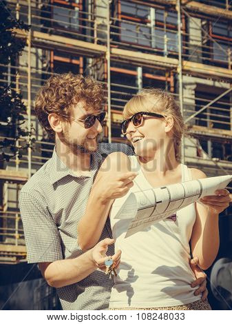 Couple On Front Of New House With Blueprint Project