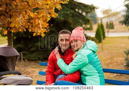Happy Couple With Baby In Carriage Outdoors