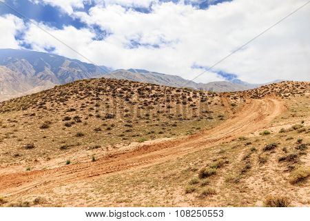 landscape of red sandstone in cloudy sky