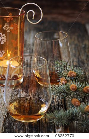 Two Glasses Of Cognac, Pine Branches And Burning Candle