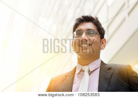 Portrait of handsome Asian Indian business man smiling, outside modern office building block, beautiful golden sunlight at background.