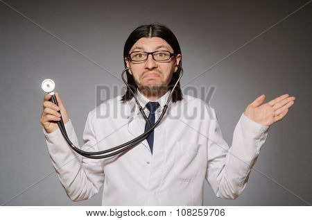 Young physician with stethoscope against gray