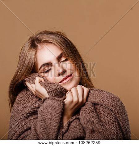 Girl Wrapped In A Warm Sweater. She Closed Her Eyes With Pleasure.