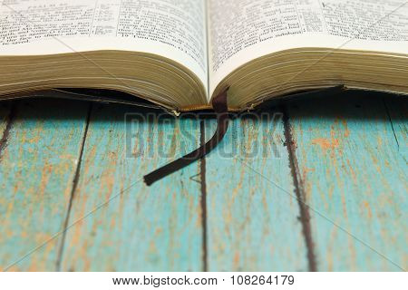 Opened Bible With A Bookmark On Wood