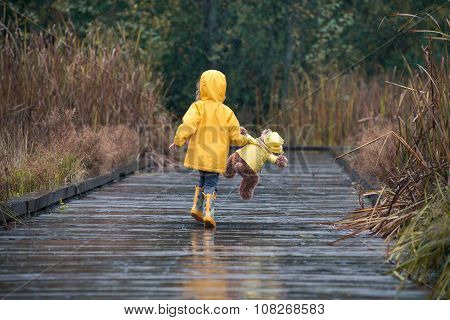 Girl With Teddy Bear In Matching Yellow Raincoats Walking In The Rain