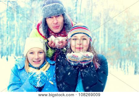 Winter Family Outdoors. Happy Joyful Family with kid blowing Snow. Wintertime, winter fun