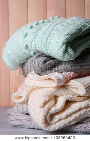 Warm clothes on wooden wall background