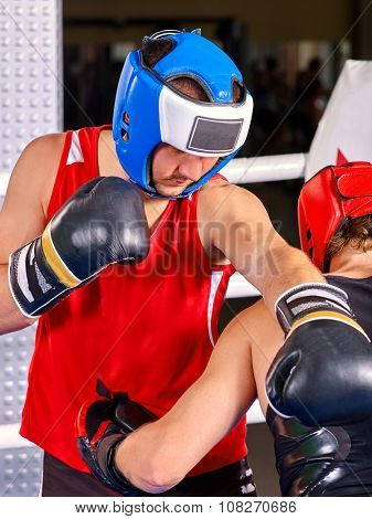 Men boxer wearing helmet and  gloves boxing on ring.