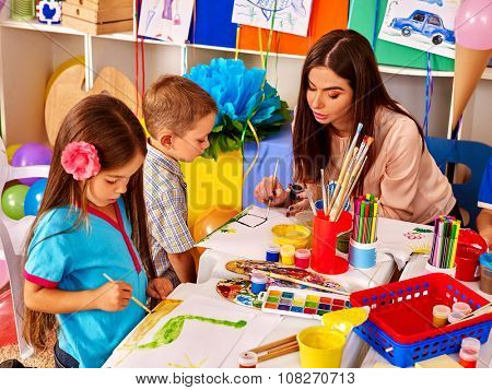 Children with teacher woman painting on paper at table  in  kindergarten . Group people.