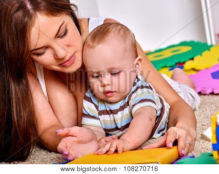 Kid baby boy lying on floor and plying with mother and puzzle toy.