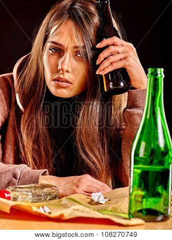 Drunk girl holding green bottle of alcohol. Soccial issue alcoholism.