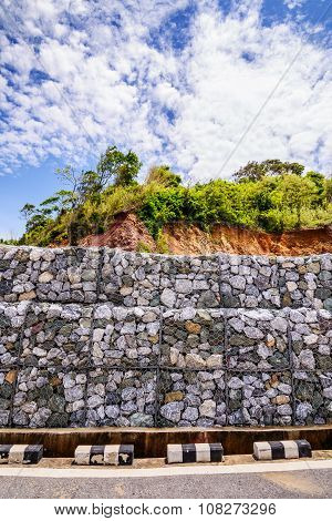 Gabion wall made of stones in the steel mesh used as a fence on a slope.