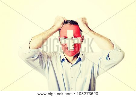 Mature man with Switzerland flag painted on face.