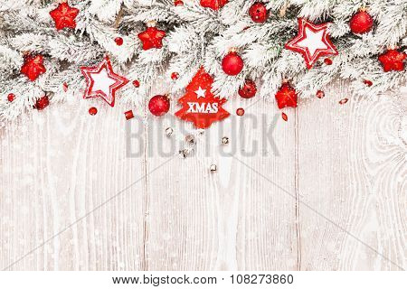 Christmas decorations in snow on white wooden background
