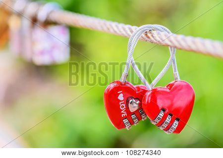 Two heart shaped love padlocks on the bridge as a symbol of eternal love and endless love.