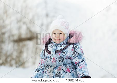 Head and shoulders portrait of toddler girl wearing white knitted hat and warm winter jacket