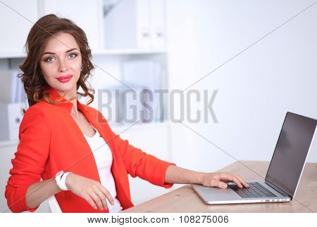 Attractive woman sitting at desk in office, working with laptop computer