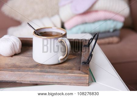 Mug of tea and warm knitted clothes in a room