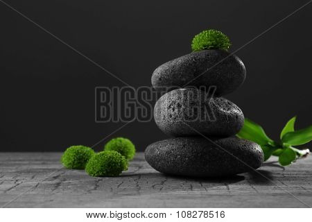 Black spa stones and green flowers, on dark grey background
