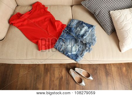 Jeans shorts with red T-shirt on sofa and ballet shoes on floor in room