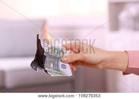 Woman burning Euros in the room