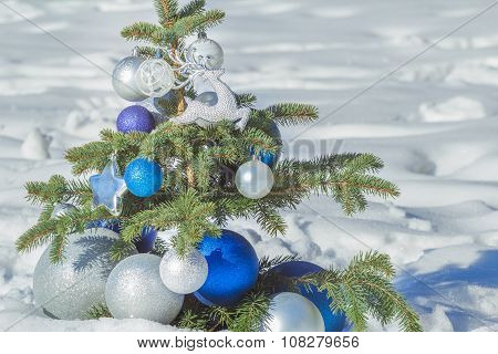 Natural fir snowy tree decorated with Christmas shiny ornaments and baubles