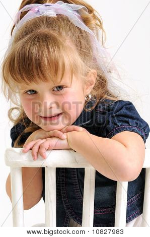 Pretty blond girl in blue dress sitting on white chair