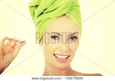 Beauty woman cleaning ear with cotton bud.