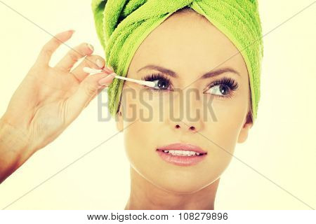 Beauty woman removing make up with cotton bud.