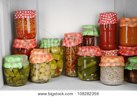 Jars with pickled vegetables and beans on wooden shelf