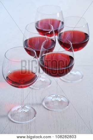 Glasses of red wine on table on bright background