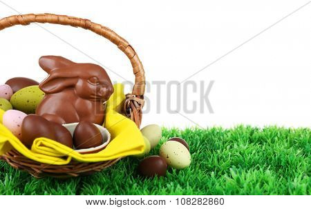 Easter chocolate bunny and eggs on green grass, on white background