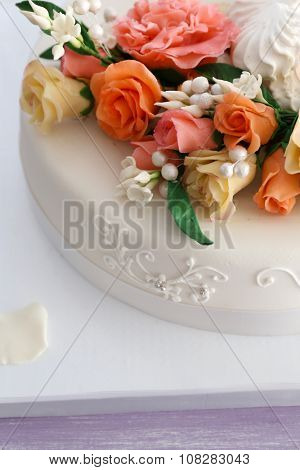 Beautiful wedding cake decorated with flowers on table in the room, close up