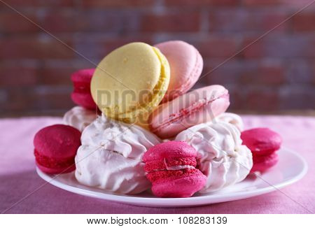 Plate with sweet cakes on pink table against brick wall background