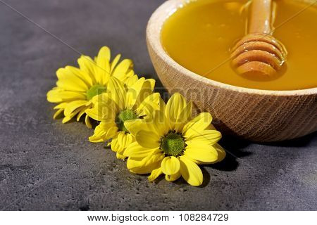 Bowl of honey, wooden dipper and flowers on dark grey background