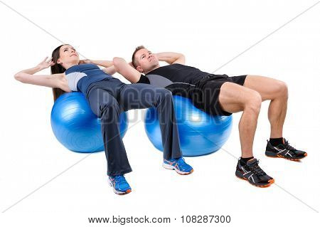 Young couple shows starting position of Abdominal Fitball Workout, isolated on white