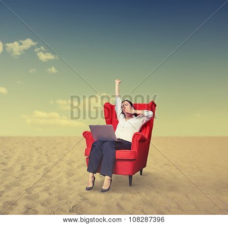 yawning businesswoman with laptop on chair working in desert