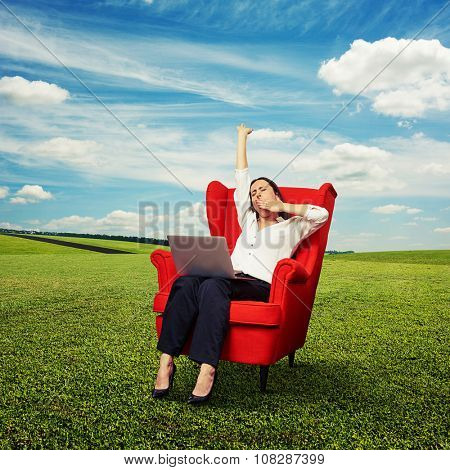 tired businesswoman sitting in red chair with laptop and yawning at outdoor
