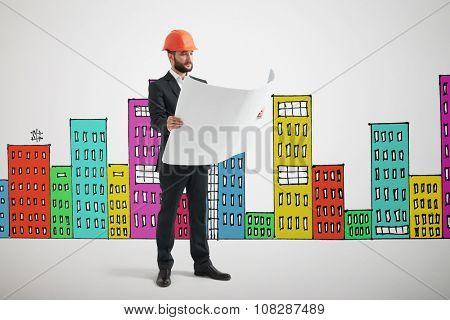 serious man in orange hardhat with blueprint over many-coloured drawing cityscape