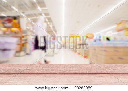 Old Wood Floor On ,blurred Defocused Background Of Generic Supermarket People Walking Shopping.