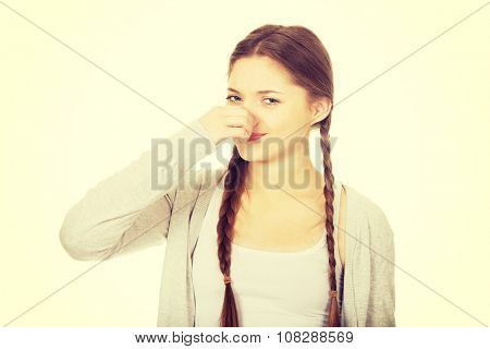 Teen woman pinchin nose because of smell.