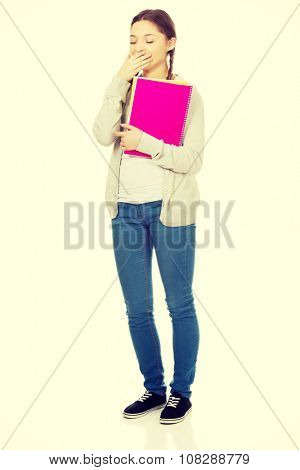 Bored yawning teen woman with notebook.