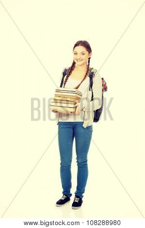 Happy teenage woman with backpack and books.