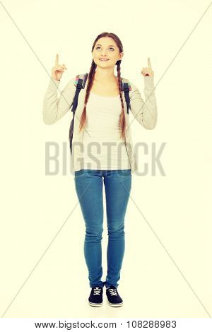 Teenager girl with school backpack pointing up.