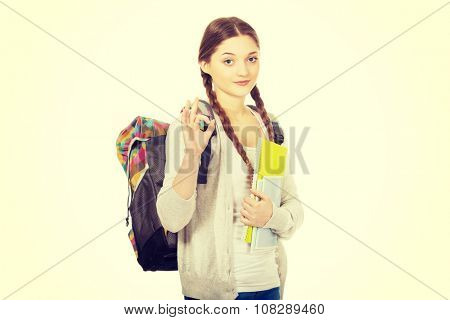 Happy teen woman with schoolbag showing perfect sign.