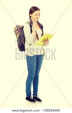 Thoughtful teenage girl with school backpack holding folders.