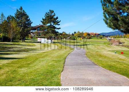 Pirin Golf Club house, green grass field, colorful autumn trees, blue sky