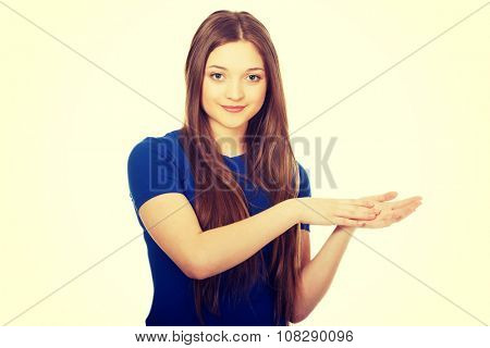 Happy teenage woman clapping hands.