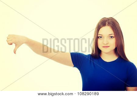 Young unhappy woman with thumbs down.